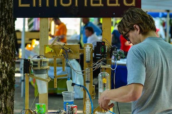 A student serves tasty soft drinks made with a machine he built himself.