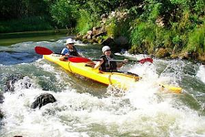Canoeing across the whitewaters of the Piusa River