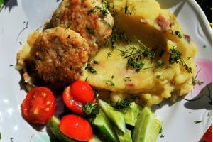 Pike cutlets with herbs, potato mash, and fresh vegetables